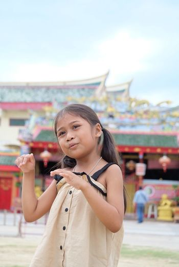 Smiling girl gesturing while standing outdoors