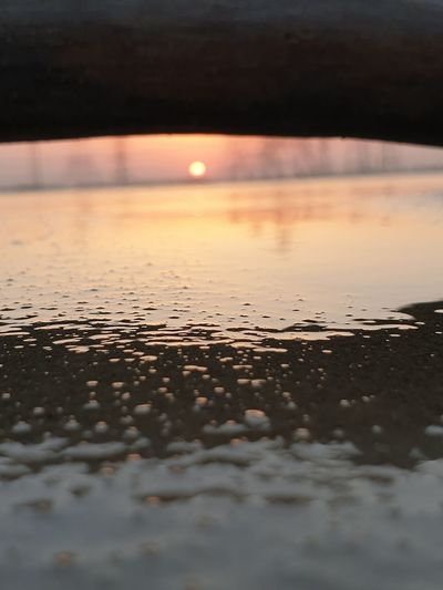 Surface level of wet shore during sunset