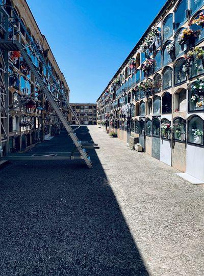 Street amidst buildings against clear blue sky