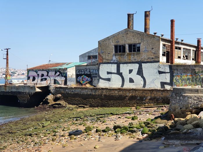 Graffiti on building by river against clear sky