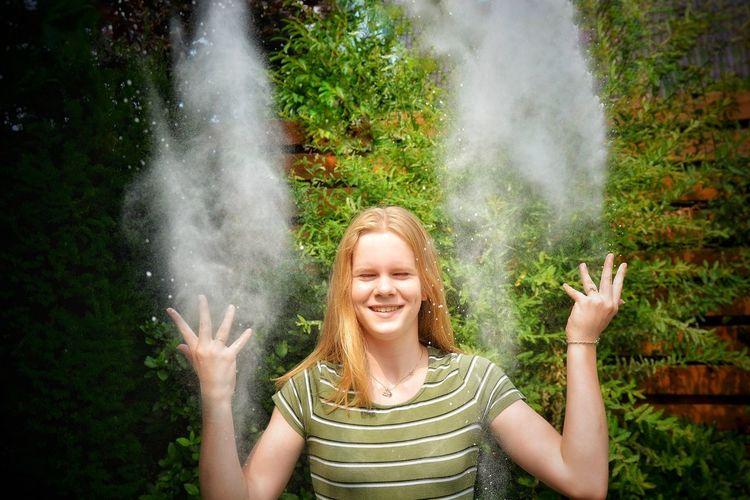 Smiling Teenage Girl Throwing Powder Against Plants