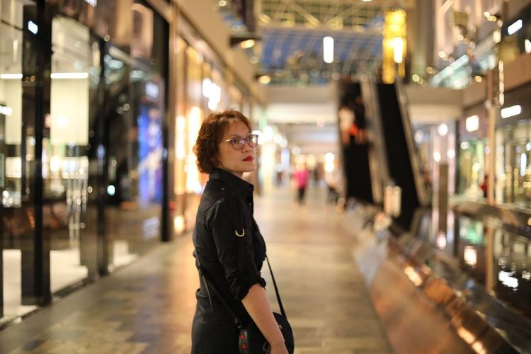 Side View Of Mid Adult Woman Looking Away While Standing In Illuminated Shopping Mall