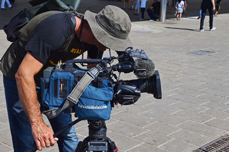 TV cameraman shooting video on street Photographer Camera - Photographic Equipment Casual Clothing Footpath Working Street Clothing Outdoors Occupation One Person Real People Men Incidental People Holding Day City Photography Themes Focus On Foreground CameraMan Camera Work Director Of Photography Shooting Tv Journalist Reporter Streetwise Photography The Art Of Street Photography