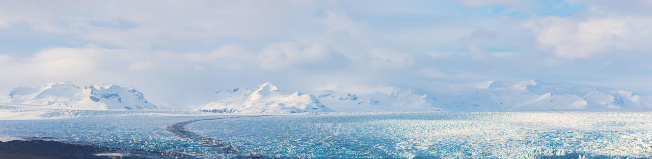 Panoramic view of snowcapped mountains by sea against sky