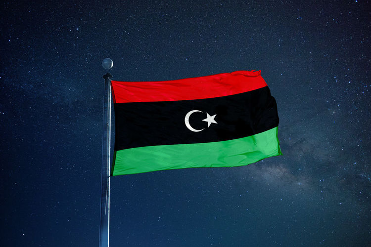 Low angle view of libyan flag against star field sky