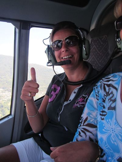 Portrait of smiling mature woman showing thumbs up in helicopter