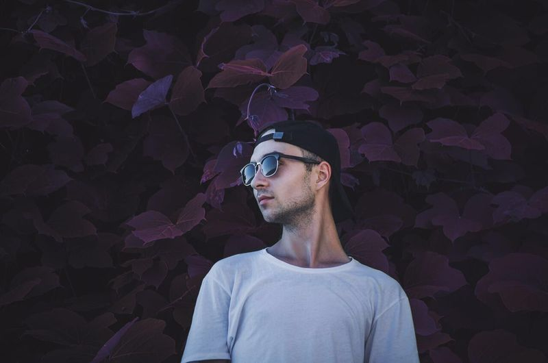 Low angle view of man wearing sunglasses standing against plants