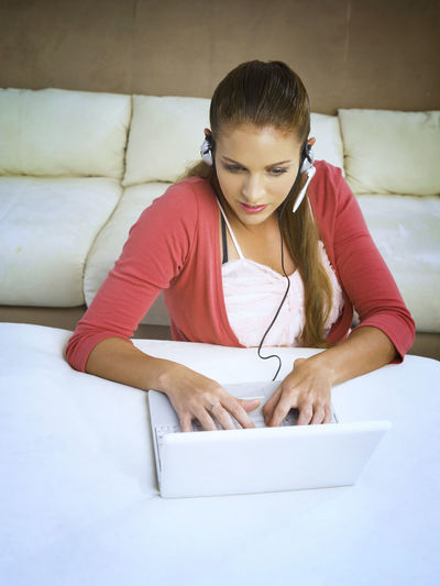 caucasian woman using laptop At Home Online Gaming Blond Hair Casual Clothing Caucasian Charting Communication Connection Ear Phone Home Interior Indoors  Laptop Leisure Activity Lifestyles Microphone One Person Onlline Real People Sitting Sofa Technology Using Laptop Wireless Technology Young Adult Young Women