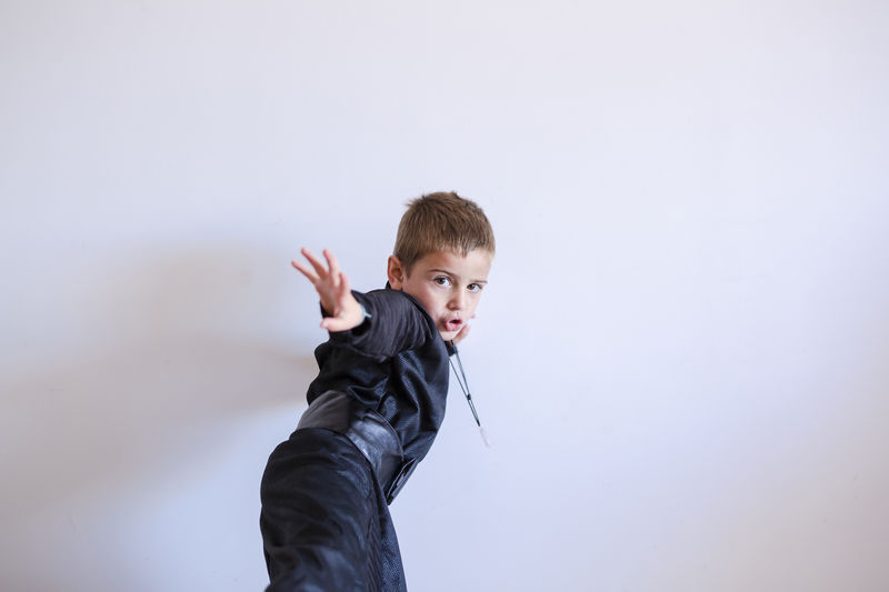 Portrait of boy standing against gray background