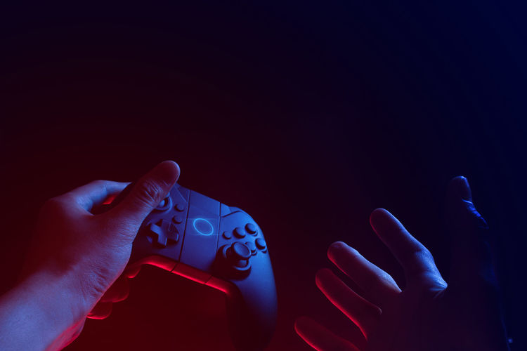 Close-up of hand holding game controller against black background