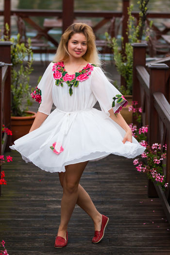 Portrait of smiling woman wearing white dress while standing on wooden footpath