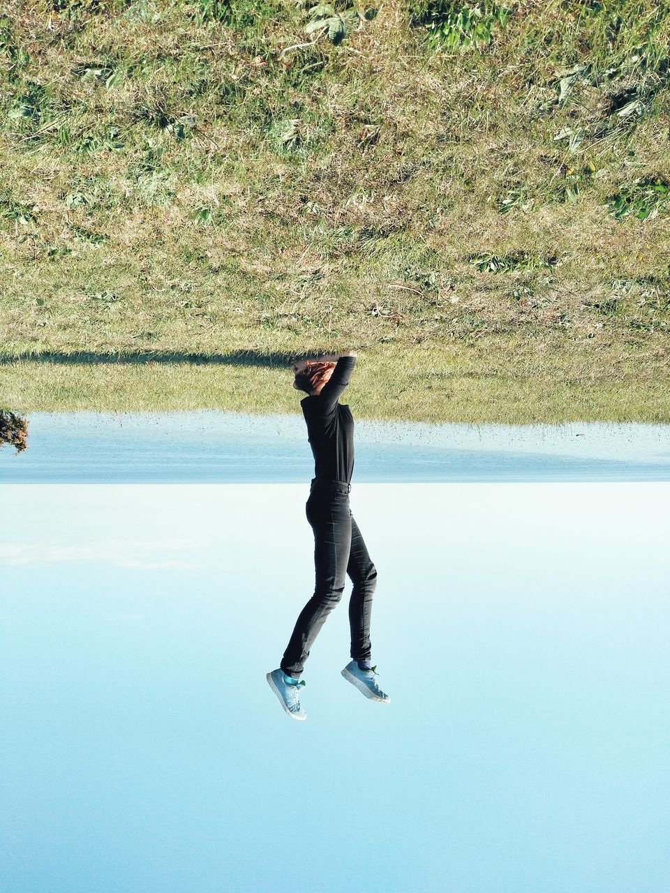 Upside Down Image Of Woman Doing Handstand At Seashore