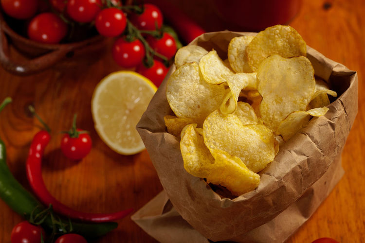 Close-Up Of Potato Chips With Cherry Tomatoes On Table