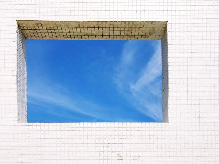 Sky seen through window of tiled wall