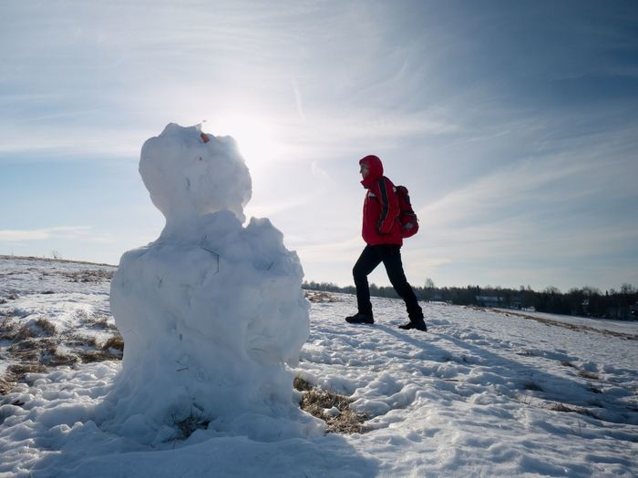 Man walk at icy snowman melting on last snowy place on spring hill. sunny spring day