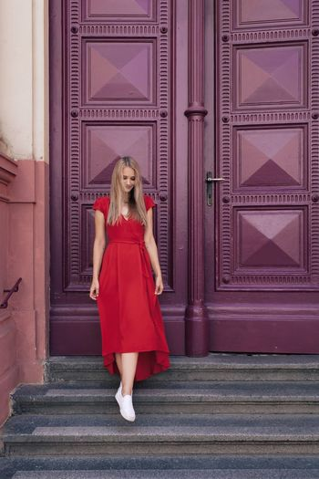 Full length portrait of woman standing against red wall