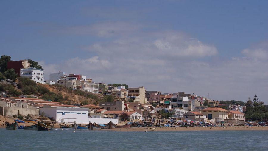 View of cityscape against calm blue sea