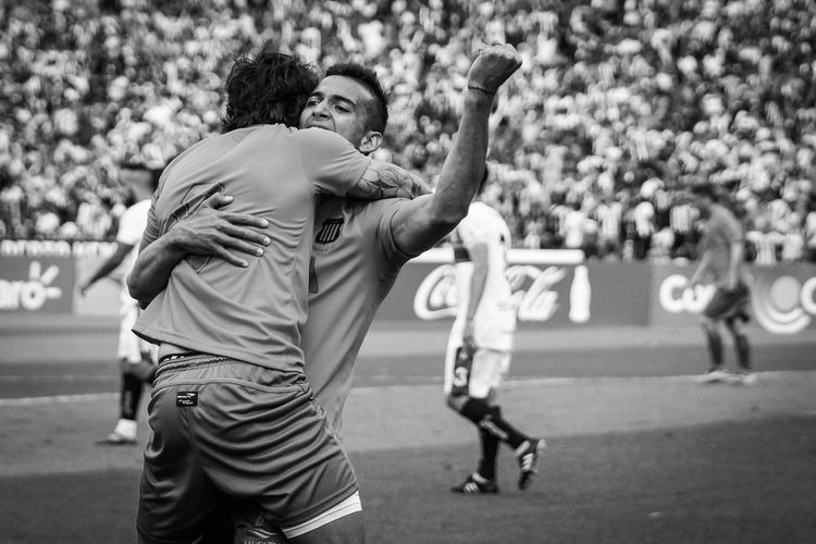 Close up of two players Talleres de Cordoba, Federal A, Victor Beraldi (T) and teammate celebrating the only goal against Union Aconquija in the Mario Kempes stadium in Cordoba, Argentina on October 19, 2015. 2015  Argentina Black And White Celebrating Color Image Cup Córdoba Federal A Fotball Fotballteam Horizontal Players Playing Real People Soccer Stadium Mario Alberto Kempe Talleres De Cordoba Two Person.