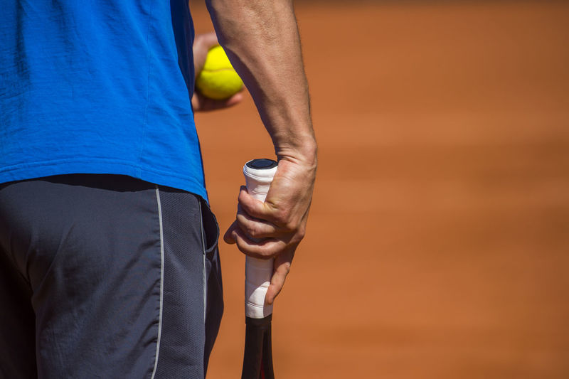 Midsection Of Player With Ball And Tennis Racket On Court