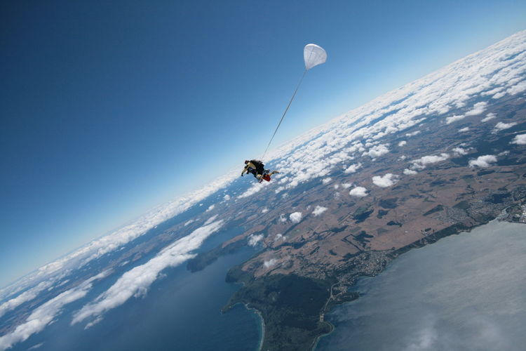 Man paragliding against clear blue sky