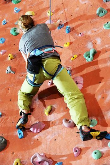 Rear View Full Length Of Woman Climbing Wall