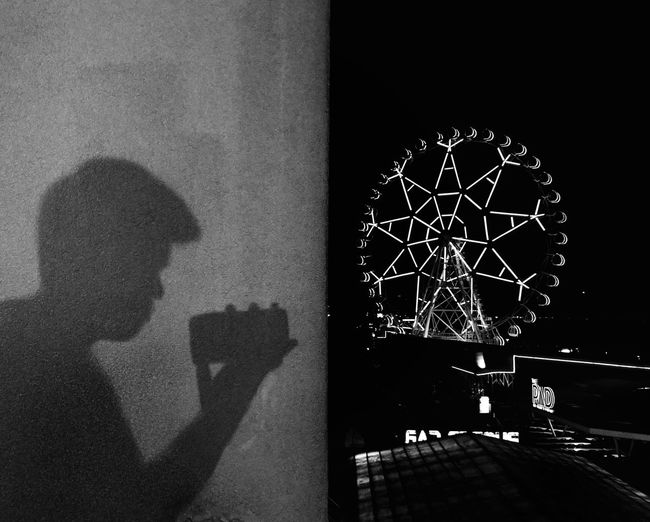 Shadow of man photographing on wall