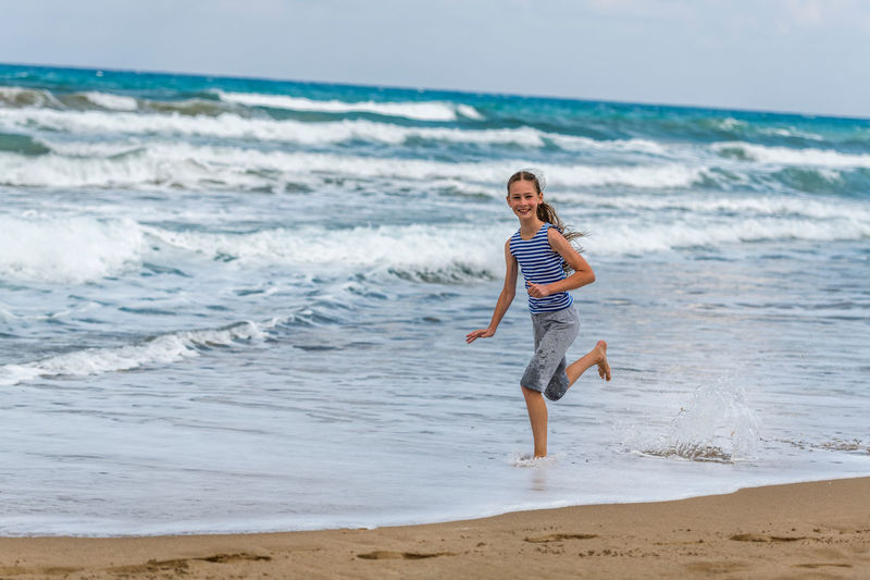 Land Sea Beach Water Motion Full Length Sand Leisure Activity Horizon Wave Horizon Over Water Casual Clothing Lifestyles Beauty In Nature People Vacations Sky Holiday Girl Running Fun Jumping