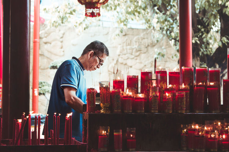 Man standing by lit candles in temple