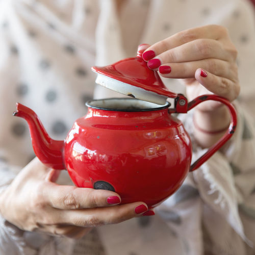 Close-up of hand holding teapot
