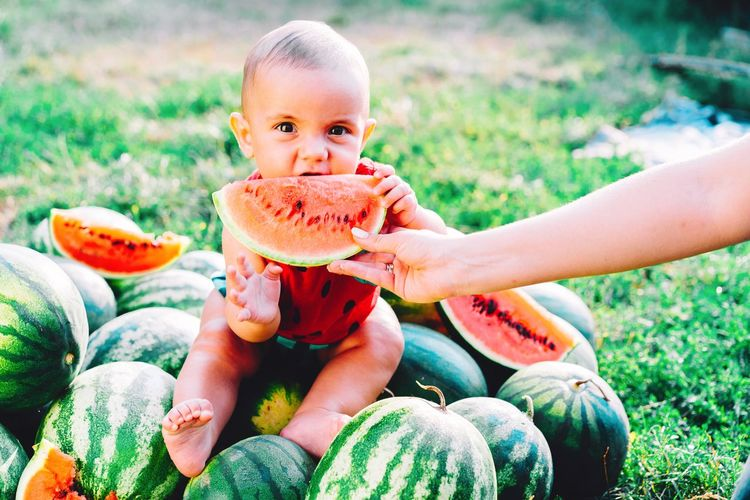 Woman giving watermelon slice to cute son at farm