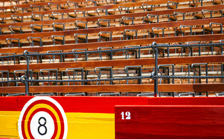 detail of the seats inside an ancient Spanish arena with wooden seats and barriers with the colors of the Spanish flag Arena Grandstands Iron Plaza De Toros Stadium Barrier Day In A Row Indoors  Large Group Of Objects No People Numbers Red Row Seat Stadium Wooden