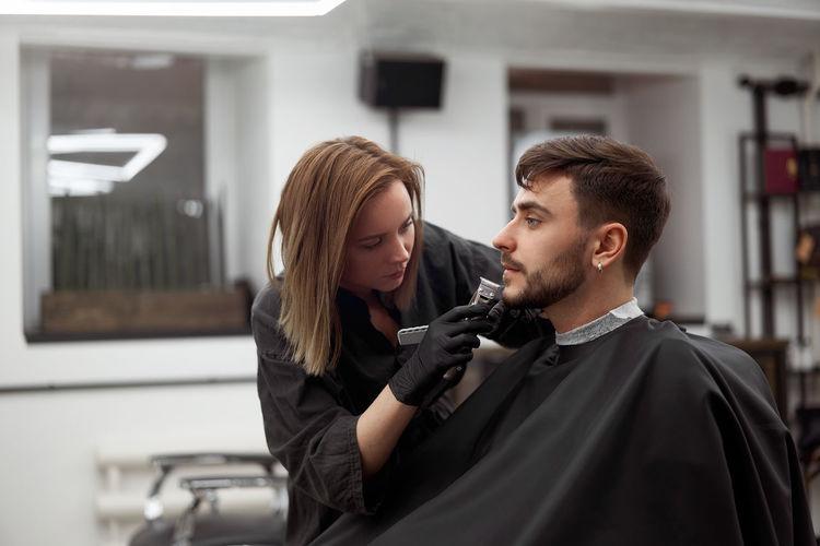 Woman shaving man beard in salon