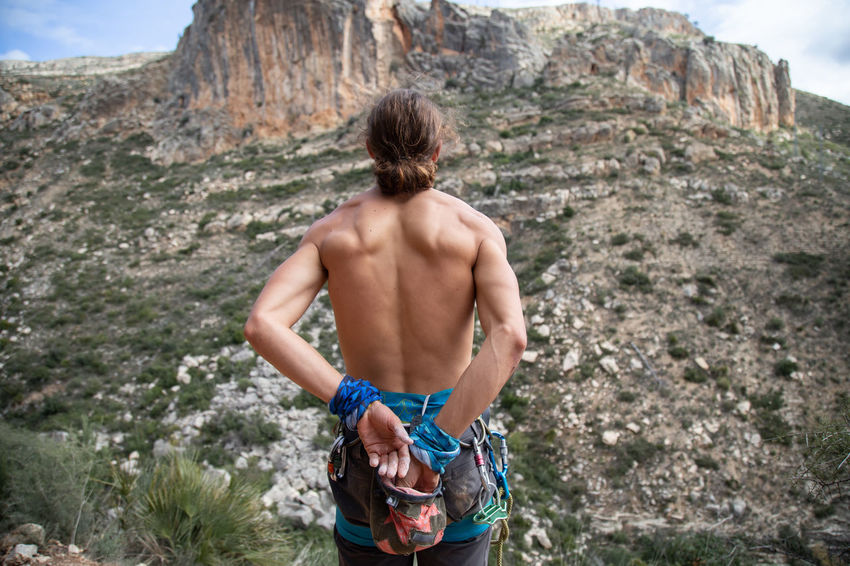 Climber man taking magnesium before climbing outdoors Close-up Hands Climbing Holding Magnesium Powder Talc Sack Handhold Rock Young Mountain Hanging Magnesia Equipment Bouldering Hand Extreme Sports Climber Preparing Sport Wall Harness Safety Standing