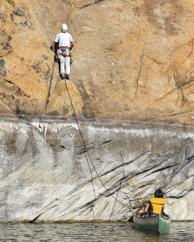 Rear view of man rock climbing