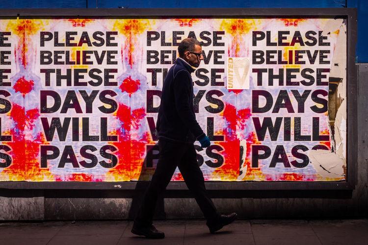 Man standing by graffiti on wall