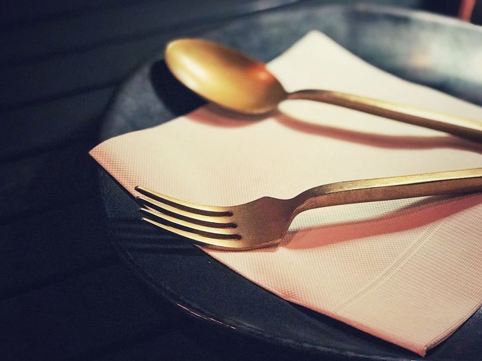 Close-up of fork and spoon and tissue in plate
