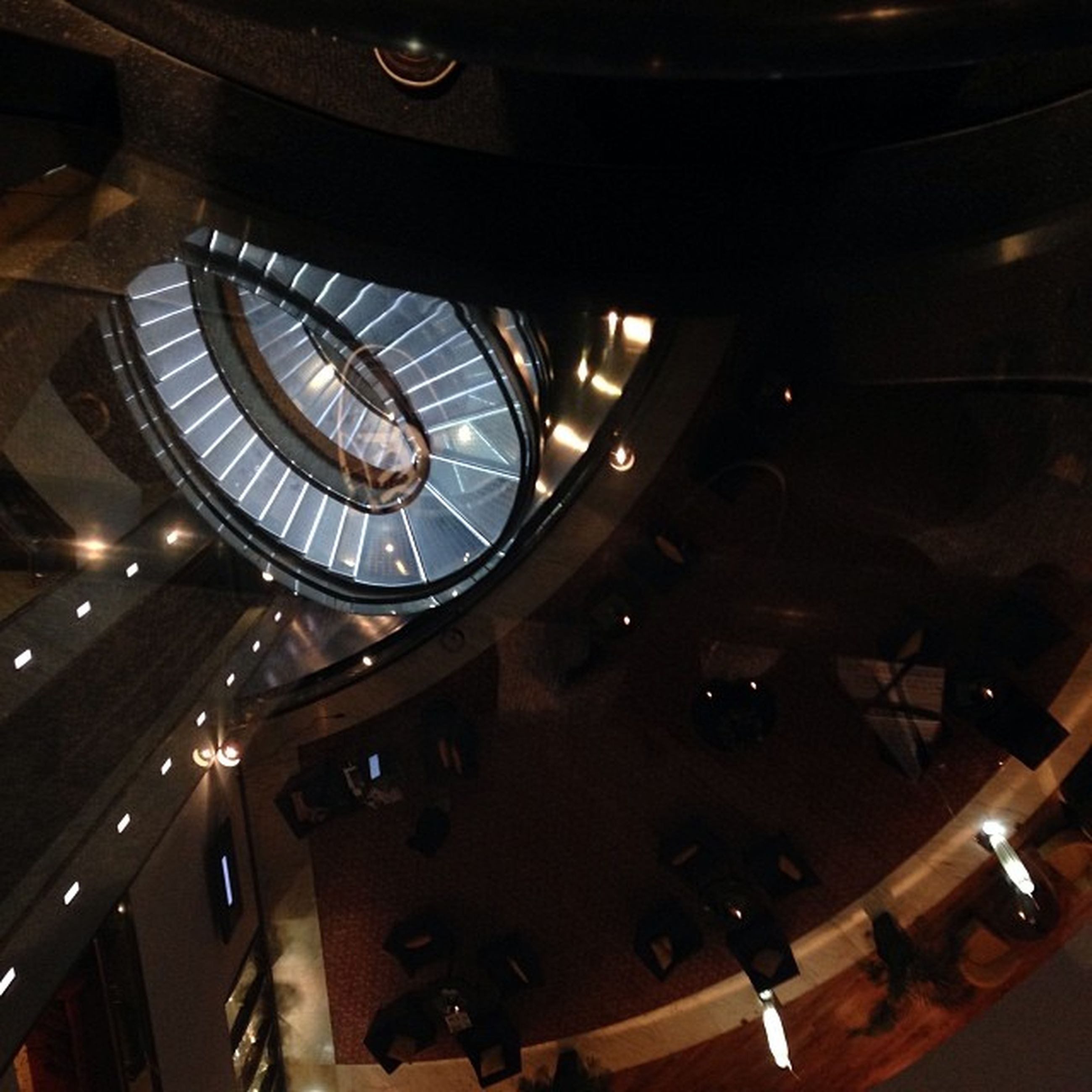 indoors, illuminated, low angle view, architecture, clock, built structure, time, ceiling, circle, glass - material, lighting equipment, technology, modern, no people, night, reflection, geometric shape, arts culture and entertainment, window, hanging