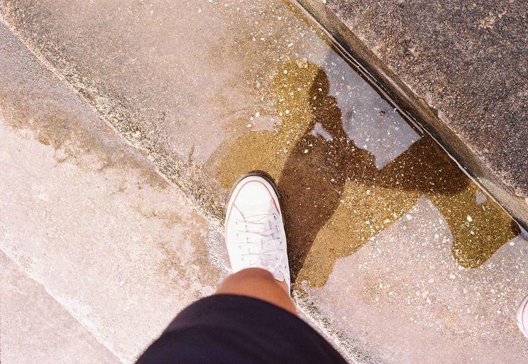 Low section of man standing on wet floor