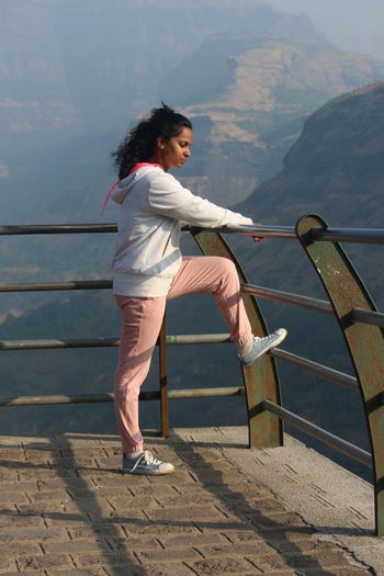 Full length of woman on railing against mountains
