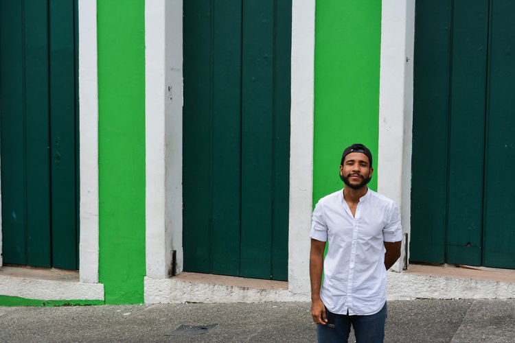 Young man standing against green built structure