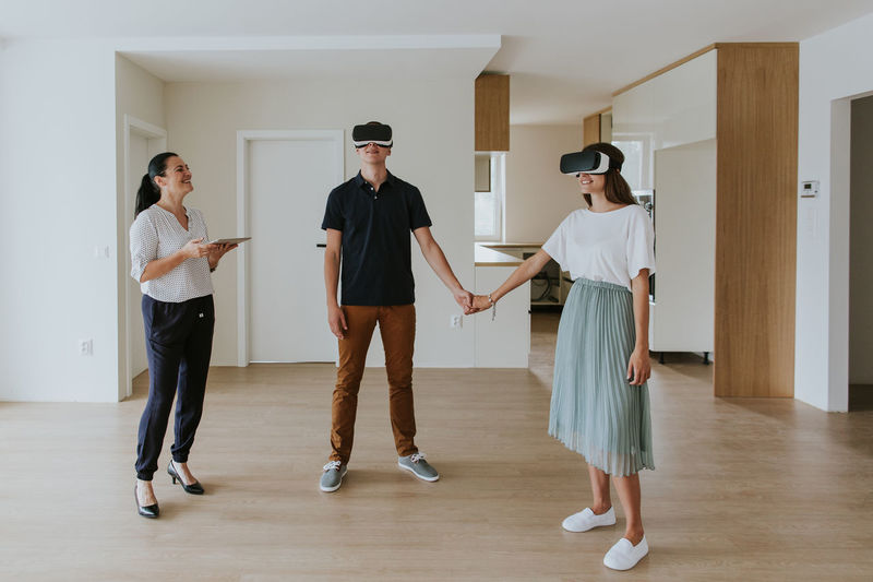 Smiling couple wearing virtual reality simulators while standing by real estate agent on floor