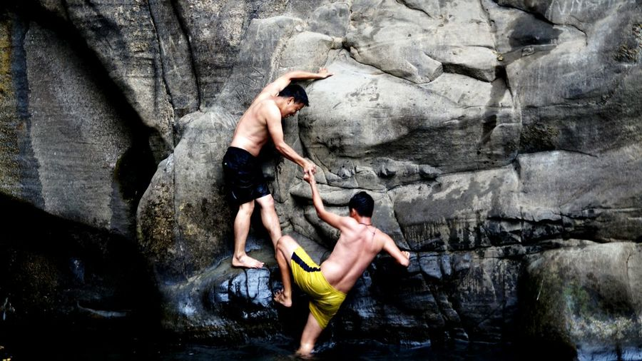 Man assisting friend in climbing on rock