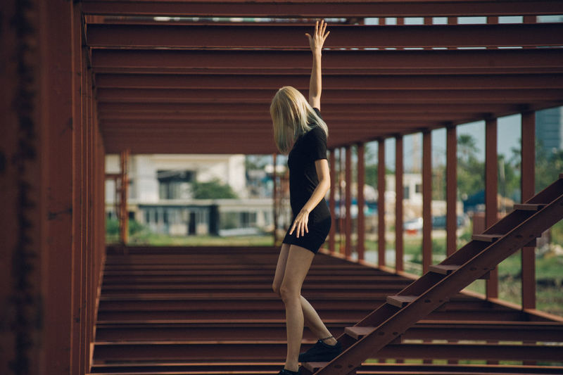Side View Of Woman Moving Down Wooden Steps