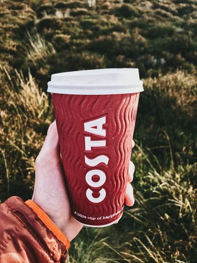 A person is pictured holding a Costa Coffee take away cup up outside in a forrest