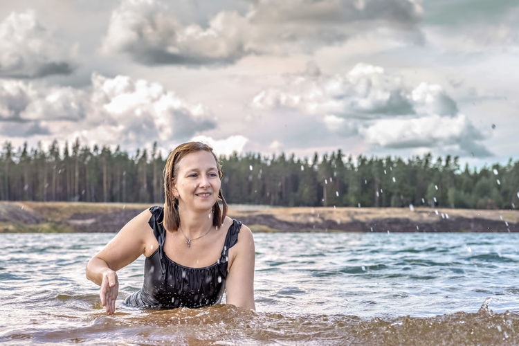 Portrait of smiling young woman against water