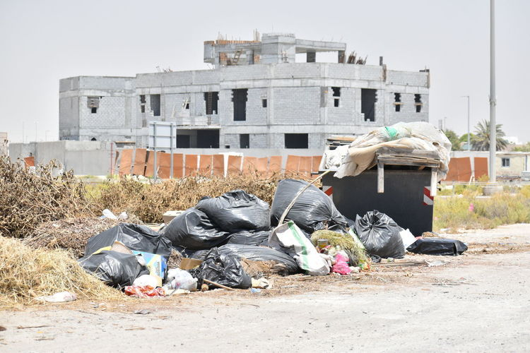 Garbage by building against sky in city