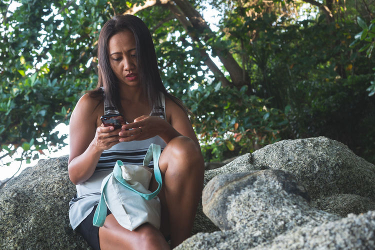 Young woman using phone while sitting on rock