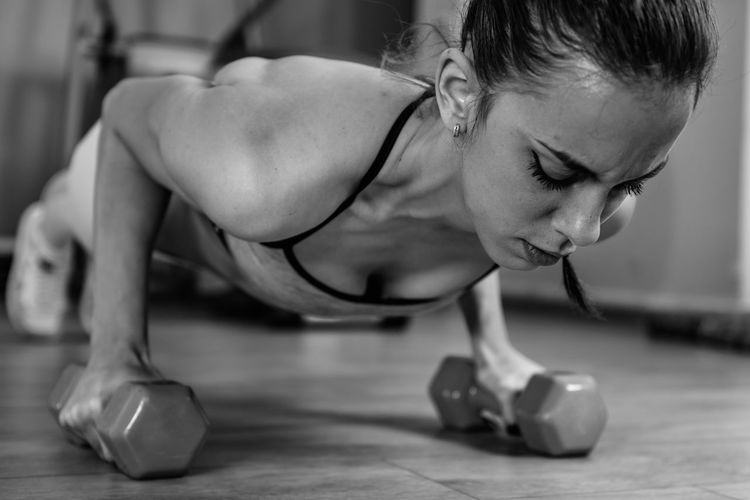 Woman doing push ups with barbells in gym