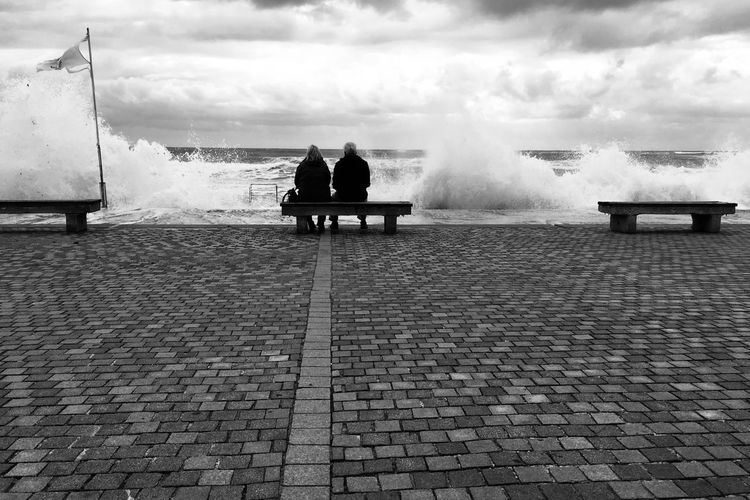 Couple watches the storm pass by Couple Couple Sitting On Bench Water Motion Real People Outdoors Sitting Sea Day Power In Nature Beauty In Nature Cloud - Sky Wave