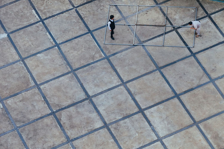 High angle view of people walking on cobblestone